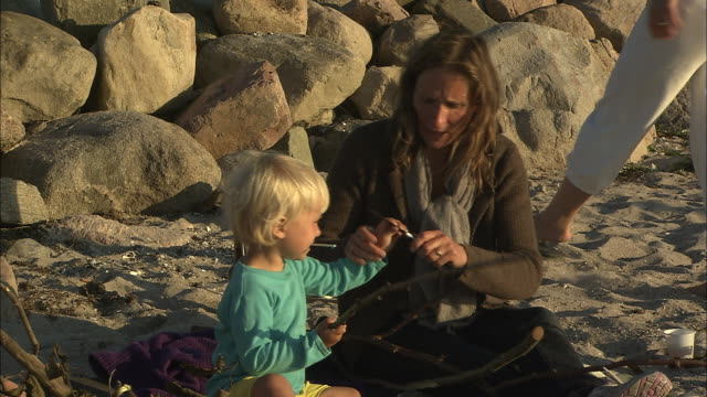 Still shot of an older woman showing a small boy how to carve up wood