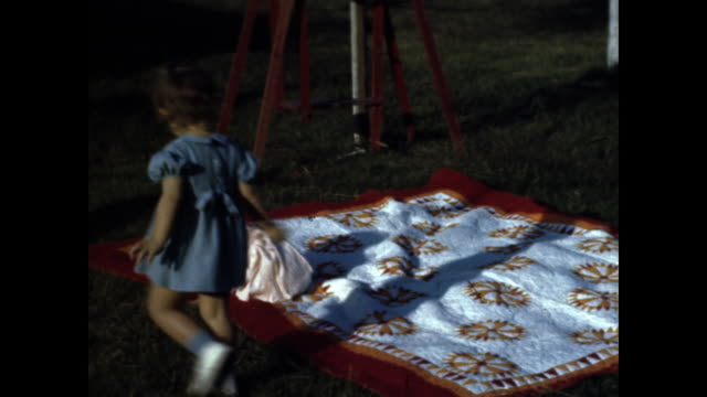 still shot of baby in pink dress crawling on blue and orange picnic blanket shot of little girl in blue dress playing with toddler - bedclothes stock videos & royalty-free footage