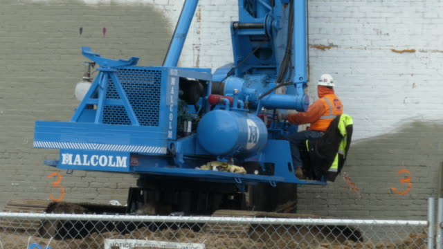 """still shot of construction worker in helmet and orange vest operating a blue construction machine, words """"malcolm"""" printed on the body - orthographic symbol stock videos & royalty-free footage"""