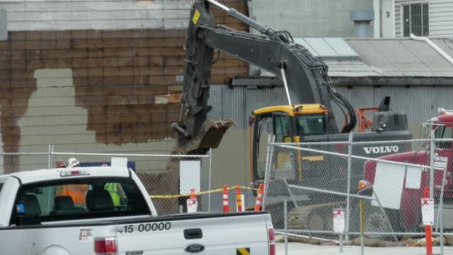 still shot of construction worker operating an excavator volvo behind metal fences other construction workers and white truck in the foreground - other stock videos & royalty-free footage