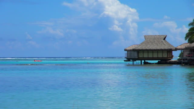 still shot of cottage and kayak in tahiti - tahiti video stock e b–roll