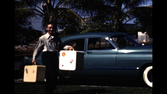 stockvideo's en b-roll-footage met still shot of family getting out of a blue car palm trees in the background they unload the car of suitcases and jackets and walk out of frame family... - bedektzadigen