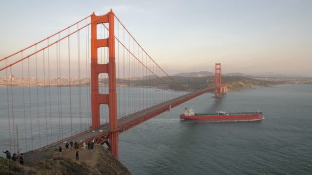 still shot of freight ship sailing under the golden gate bridge and city in background at sunset, san francisco, california, united states of america, north america - golden gate bridge stock-videos und b-roll-filmmaterial
