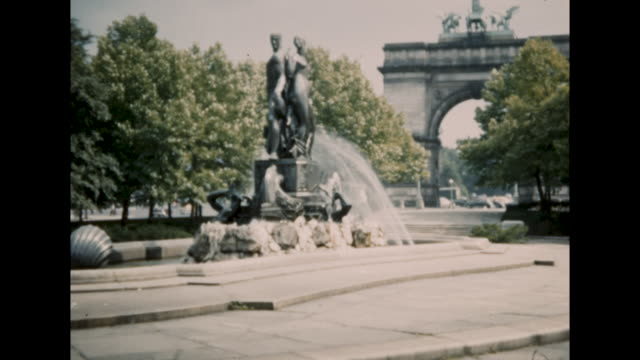 still shot of large arch across the street, lots of cars driving on the street; still shot of fountains with statue of people - the cars stock videos & royalty-free footage