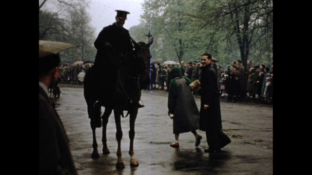still shot of man in officer uniform on horse talking with couple on the street people standing in the background with umbrellas fog and trees - ウマ科点の映像素材/bロール