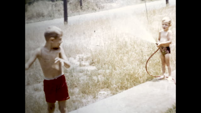 still shot of one boy watering another boy with a water hose laughing and looking at the camera - shirtless stock videos & royalty-free footage