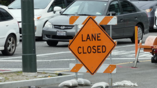 """still shot of orange sign on the street """"lane closed"""" with sandbags on top; cars pass in the street and tent on the sidewalk in the background - pavement stock videos & royalty-free footage"""