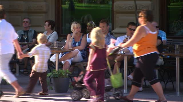 vídeos de stock e filmes b-roll de still shot of people enjoying food and drinks outside in the shade. - finlândia