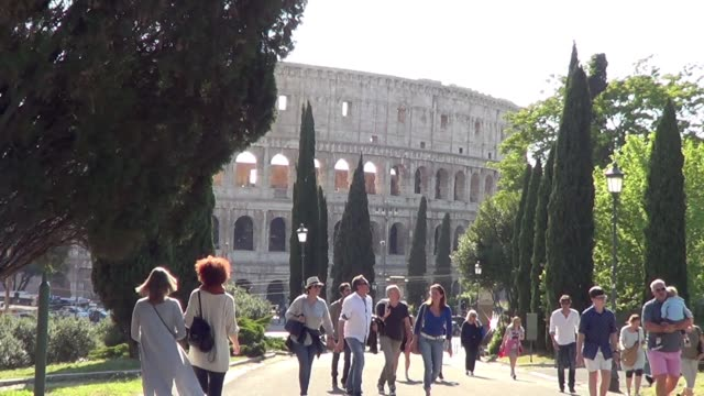 still shot of people walking with the colosseum in the background in rome, italy - colosseo video stock e b–roll