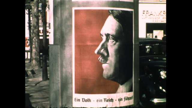 still shot of posters of hitler on pole on the street; people sitting on the bench and walking on the street in the background; nazi swastika flags... - nazi swastika stock videos & royalty-free footage