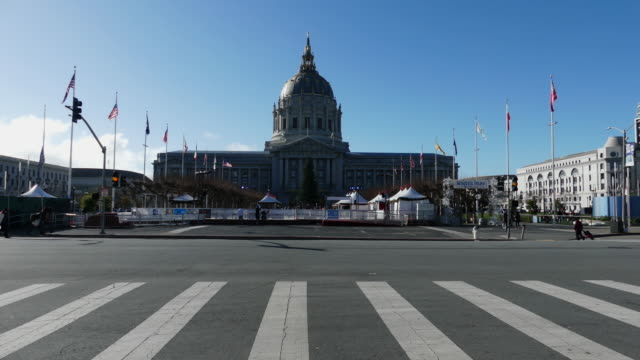 still shot of the civic center with tents and banners in front of it crosswalk and people crossing in the foreground - winter点の映像素材/bロール