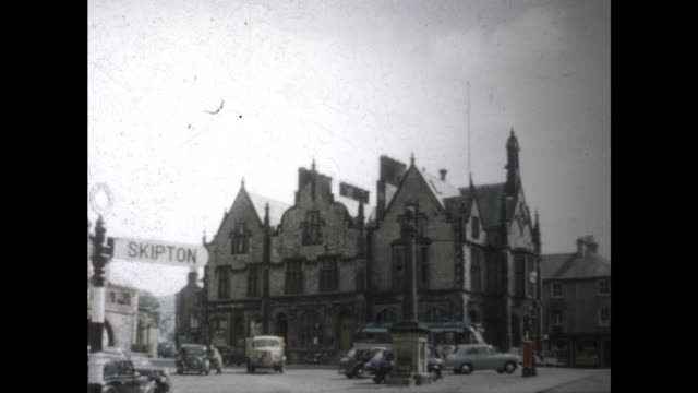 """still shot of three identical buildings in a row, banner """"skipton""""; cars parked in front of the building and people walking - スキップトン点の映像素材/bロール"""