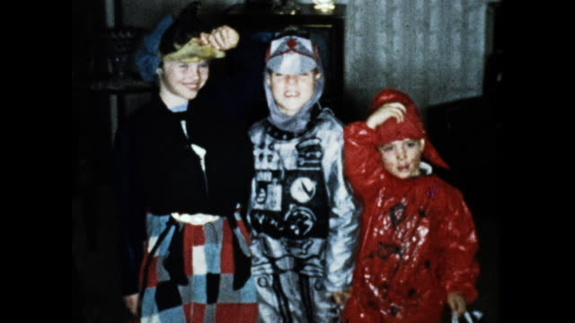 still shot of three kids in halloween costumes posing for the camera in the living room - children only stock videos & royalty-free footage