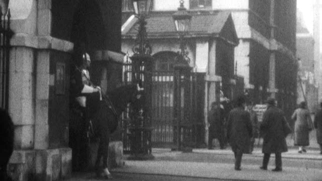 still shot of two knights in armor and on horseback standing next to a gate people passing on the street keep looking at them - 1925 stock videos & royalty-free footage