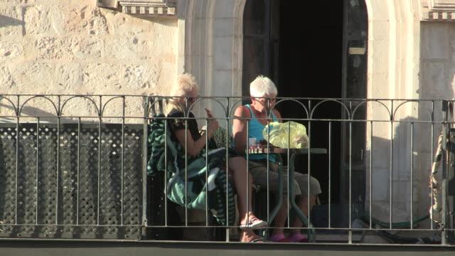 still shot of two older women sitting next to a railing. no audio - 聖地パレスチナ点の映像素材/bロール