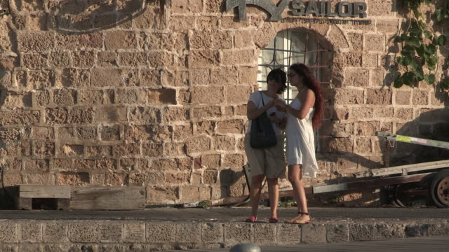 still shot of two women deciding where to go near the port - jaffa stock-videos und b-roll-filmmaterial