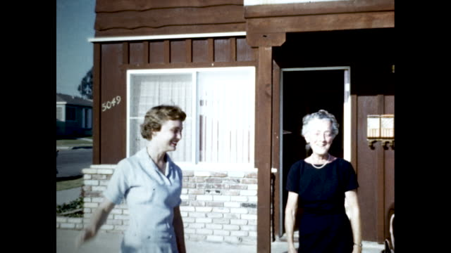 still shot of two women in dresses one with grey hair and one young smiling and talking while exiting a brown house waves the camera goodbye and... - hair clip stock videos & royalty-free footage