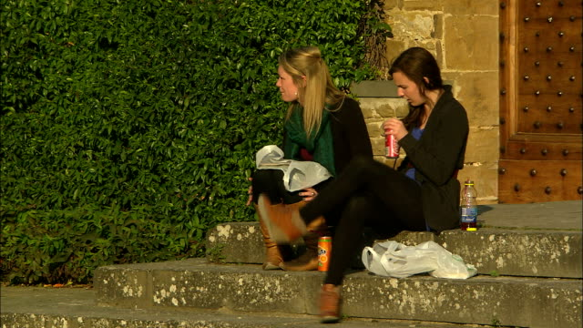 Still shot of two young women on a stoop snacking