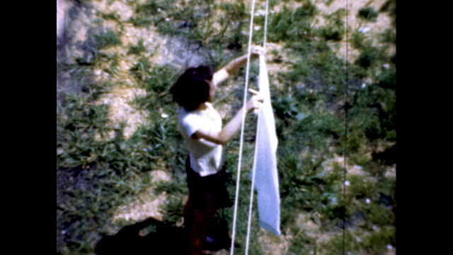 still shot of woman with black hair hanging a white piece of clothes on a clothesline; she smiles and waves at the camera - housework stock videos & royalty-free footage