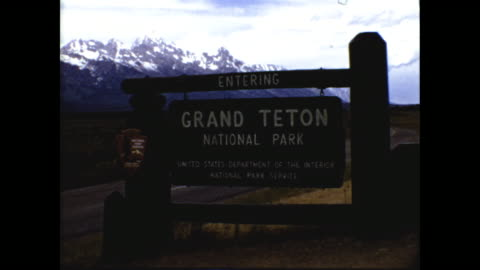 """still shot of wooden sign """"entering grand teton national park"""" """"united states department of the interior national park service""""; panning shot of... - teton range stock videos & royalty-free footage"""