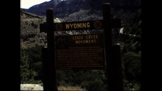 """still shot of wooden sign """"wyoming leigh creek monument""""; tilt up shot of the creek and the mountains and forests - wyoming stock videos & royalty-free footage"""