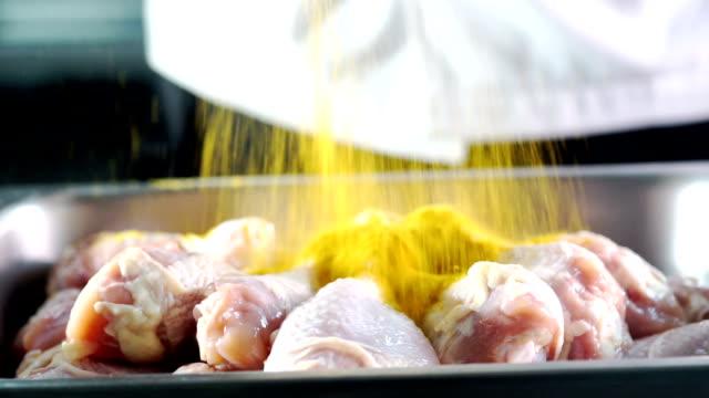 vídeos de stock, filmes e b-roll de ecu ainda tiro: derramando caril em pó para as pernas de frango cru para cozinhar. - curry powder