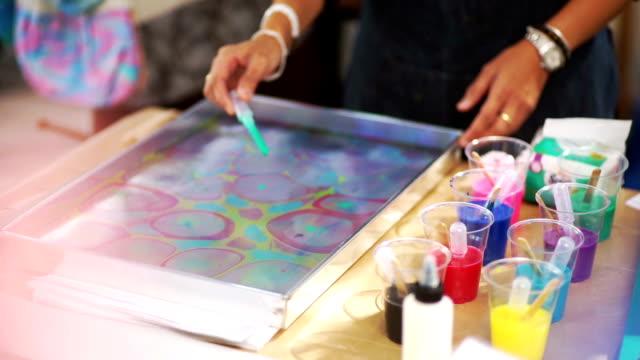 vídeos y material grabado en eventos de stock de ms still shot: mano de mujer con pipetas y puntos de goteo y aplicando nuevos colores en el agua, el proceso de los tejidos de veteado en taller de artesanía. - marmolizado