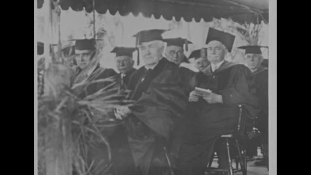 VS stills inventor Thomas Edison sitting in cap academic robe and academic hood at ceremony at which he received an honorary Doctor of Science degree