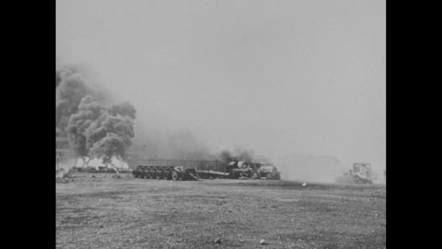 VS stills smoke and fire at Hickam Field during the attack / the damaged tail of an airplane and destroyed hangar behind / airplane engine partially...