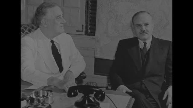 president franklin roosevelt, seated at desk during white house meeting with soviet foreign minister vyacheslav molotov, who sits in front of map;... - disco combinatore video stock e b–roll