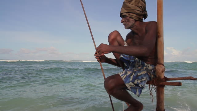 ms stilt fisherman (pole fisherman) checking his fishing rod before fishing for sardines / hikkaduwa, southern province, sri lanka - sri lankan culture stock videos & royalty-free footage