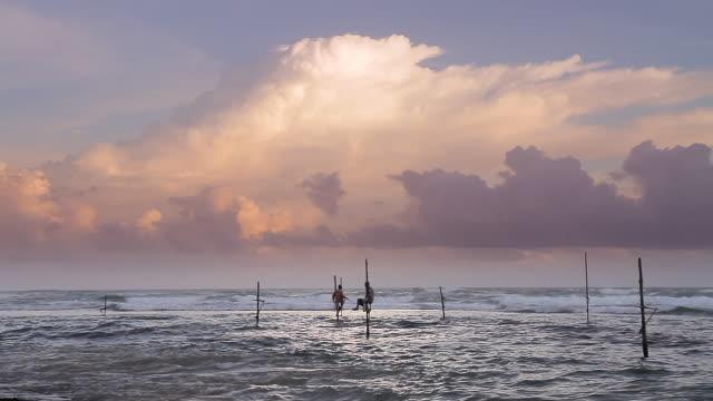 WS Stilt fishermen (pole fishermen) casting for sardines and thunderhead cloud at sunset / Ahangama, Southern Province, Sri Lanka