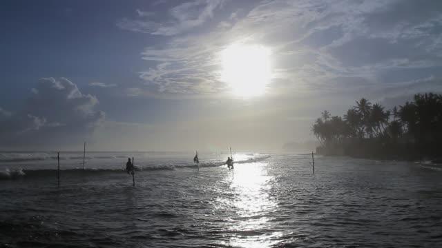 MS Stilt fishermen (pole fishermen) silhouetted against sun / Ahangama, Southern Province, Sri Lanka
