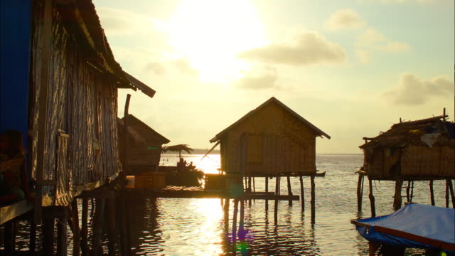 stilt houses on water and a boat in indonesia - stilt house stock videos & royalty-free footage