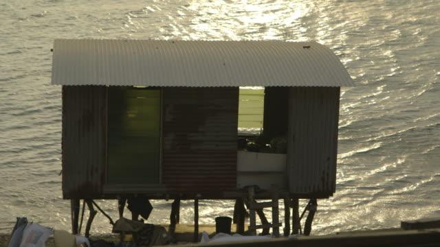 stilt shack house at a coastline, moresby, papua - stilt house stock videos & royalty-free footage