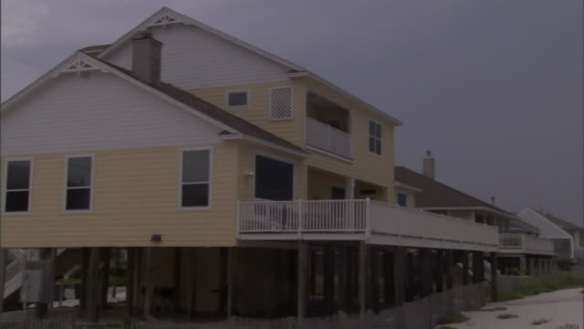 stilts hold up a yellow home on beachfront property. - stilts stock videos and b-roll footage
