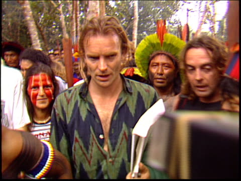 Sting walks through a crowd of Kayapo Indians and reporters after a press conference to save the rainforest
