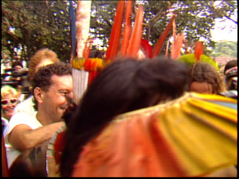 sting walks through a crowd of kayapo indians and reporters after a press conference to save the rainforest a man shouts at people to clear the way - yanomami stock videos and b-roll footage