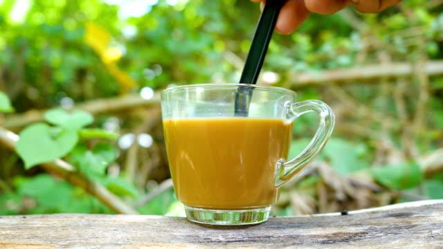 Agregue el café caliente vidrio transparente con fondo de naturaleza verde, Dolly Shot