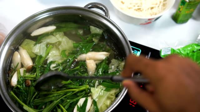 stir sukiyaki at home with ladle - sukiyaki stock videos and b-roll footage