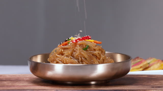 stir-fried korean chili peppers and pork (or japchae, korea traditional festival foods) with sesame in the bowl - savory food stock videos & royalty-free footage