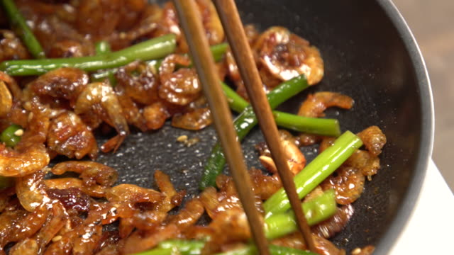stir-frying baby anchovies with shishito peppers / south korea - spraying stock videos & royalty-free footage