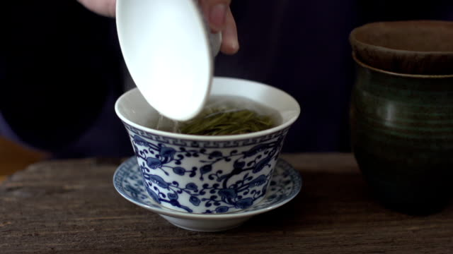 stirring a cup of tea with tea lid,Slow Motion