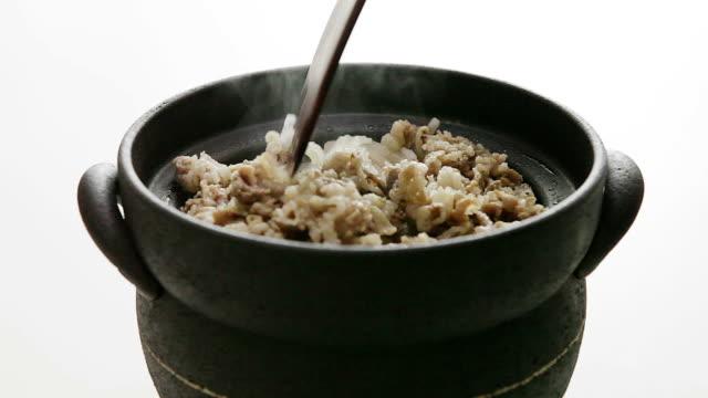vídeos de stock, filmes e b-roll de stirring beef and rice with wooden spatula (sogogimudolsotbap beef radish stone pot rice) (korean traditional food) - espátula