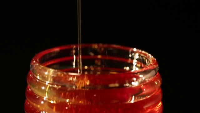 vídeos de stock, filmes e b-roll de stirring honey inside pot - mel