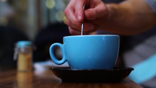 Stirring Mug of Coffee in Cafe