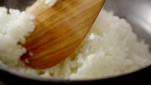 stirring rice with wooden rice paddle - reis grundnahrungsmittel stock-videos und b-roll-filmmaterial