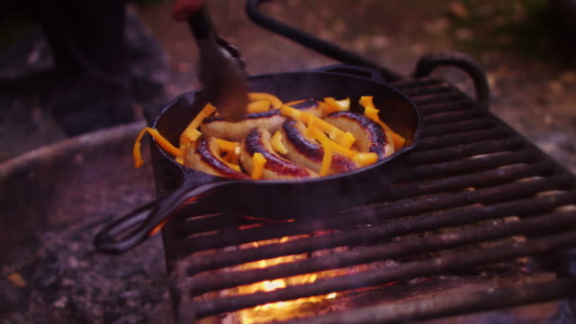 stirring sausages and bell peppers in cast iron pan on campfire - cast iron stock videos and b-roll footage