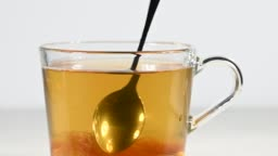 Stirring sugar with spoon in cup of green tea