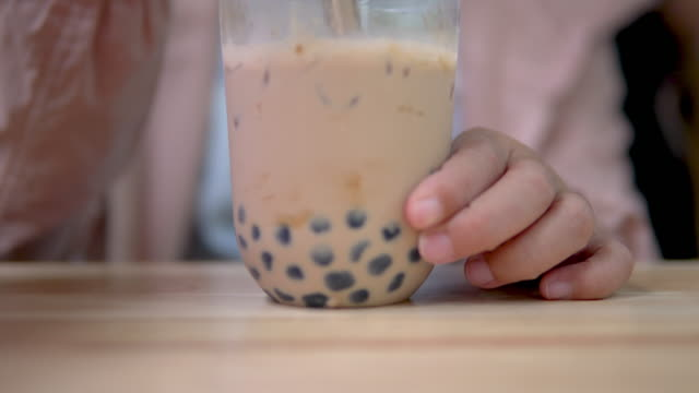 stirring taiwan bubble milk tea with plastic straw on the table. - milk tea stock videos & royalty-free footage